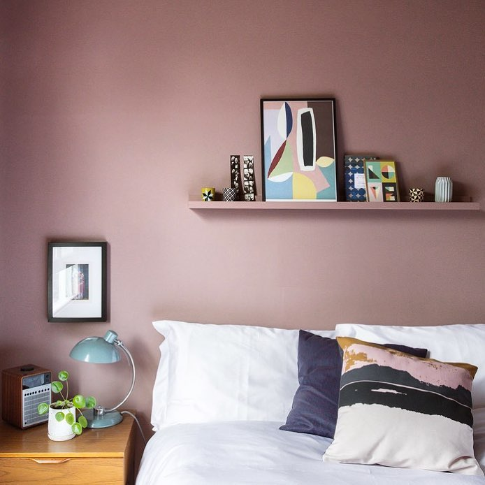 Pink bedroom feature wall with abstract cushions a prints